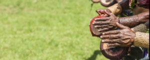 Photo of mens hands from papua new guinea drumming on rights hand side of photo with green grass in the background