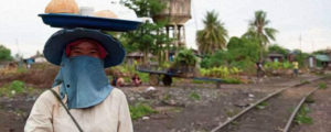 Photo of Cambodian woman with cloth around her face and wearing hat with tray of food on top of her head. Behind her is a railway line.