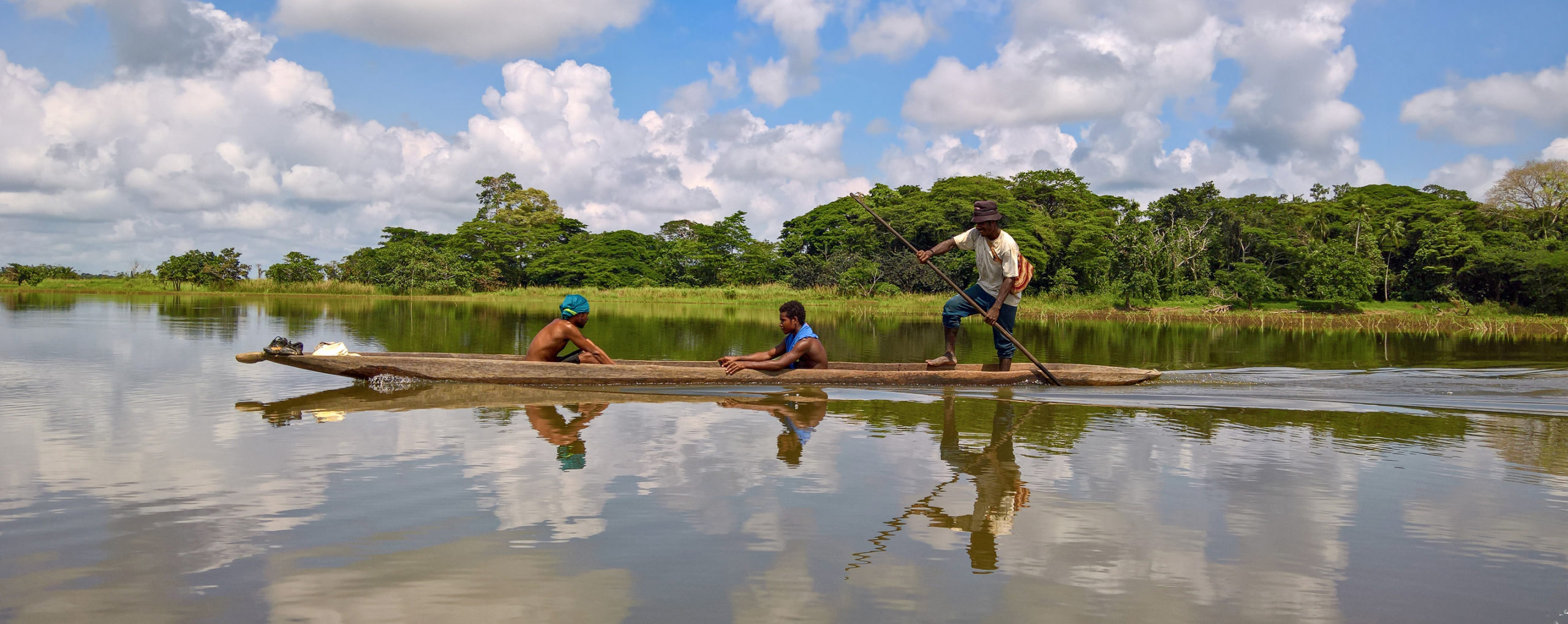 Photo of three Indigenous men in their traditional canoe travelling down the Sepik River in Papua New Guinea